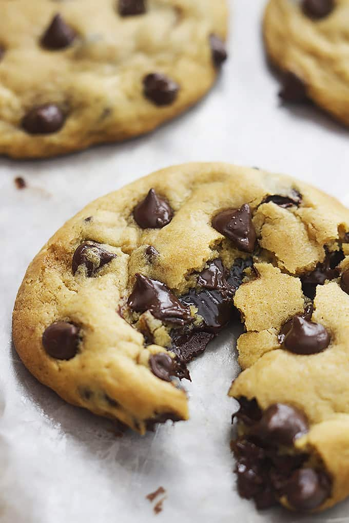close up of a hot fudge stuffed chocolate chip cookie broken in half with more cookies on the side.