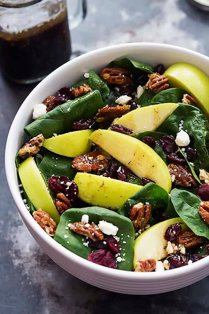 a bowl of apple cherry candied pecan salad with sweet balsamic dressing in a jar on the side.