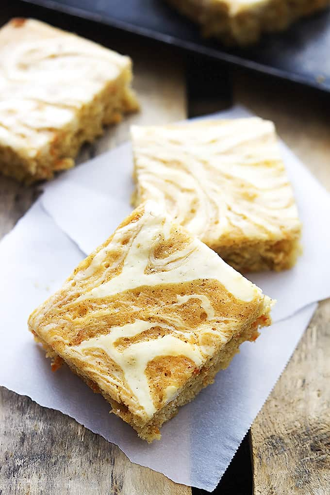 stacked cream cheese swirled carrot cake bars with another bar on the side.