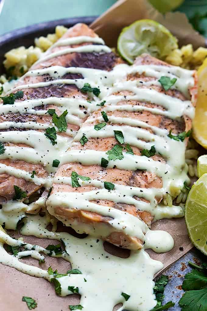 close up of baked salmon with avocado cream sauce.
