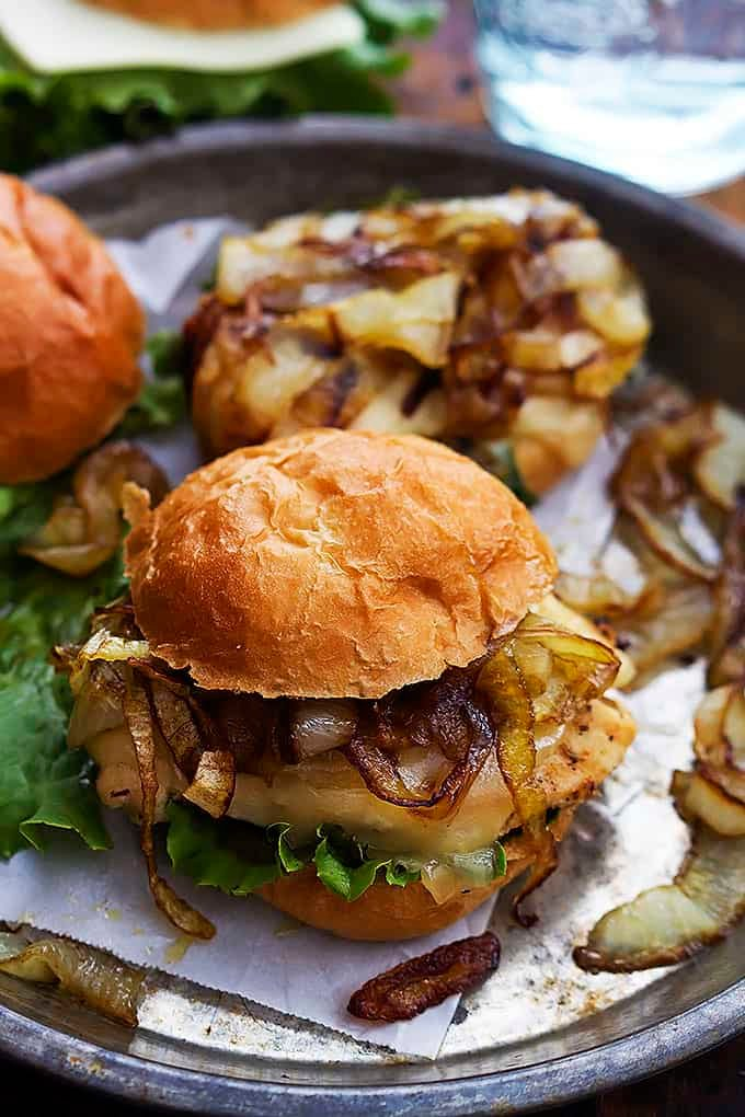 a French onion chicken slider with onions and another slider on a round serving tray.