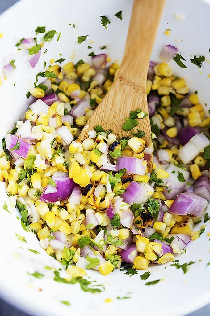 top view of grilled corn salsa with a wooden serving spoon in a bowl.