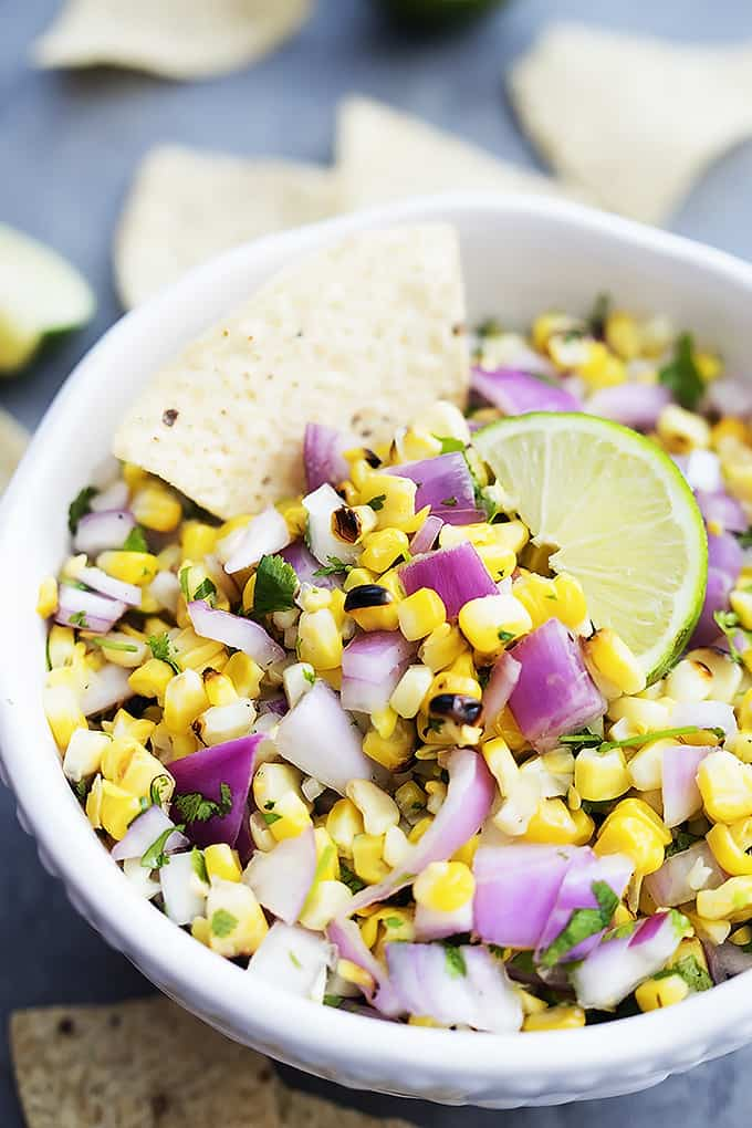 a bowl of grilled corn salsa with a chip dipped in it.