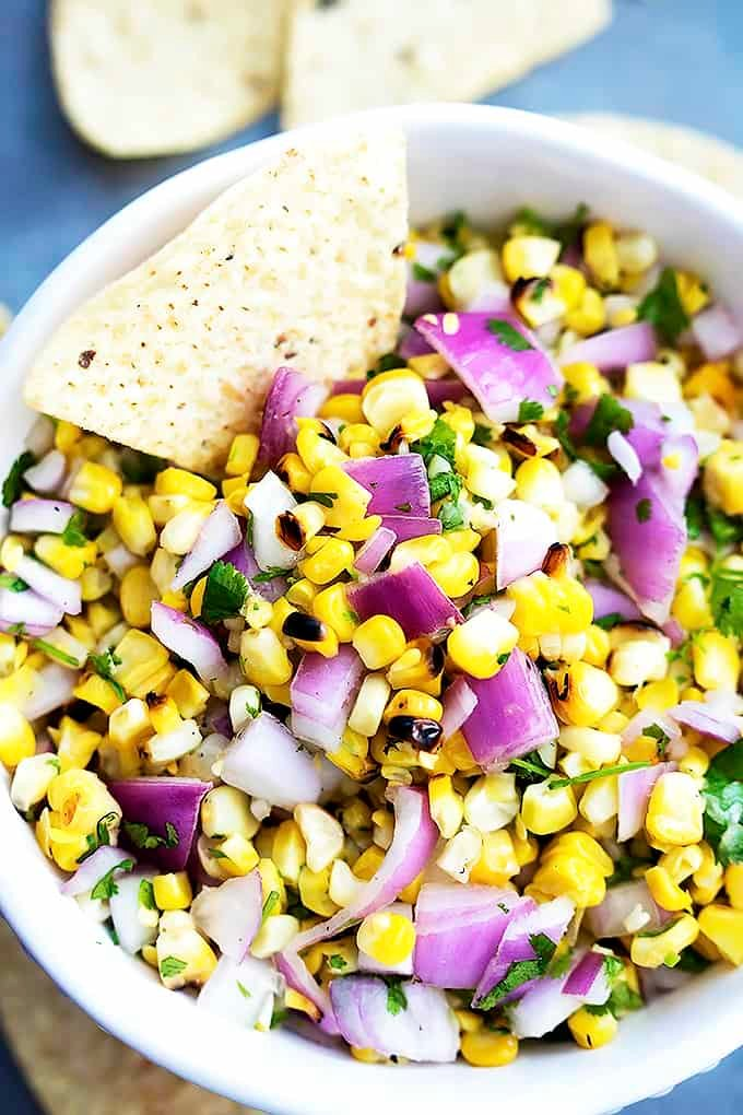 top view of grilled corn salsa in a bowl with a chip dipped in it.