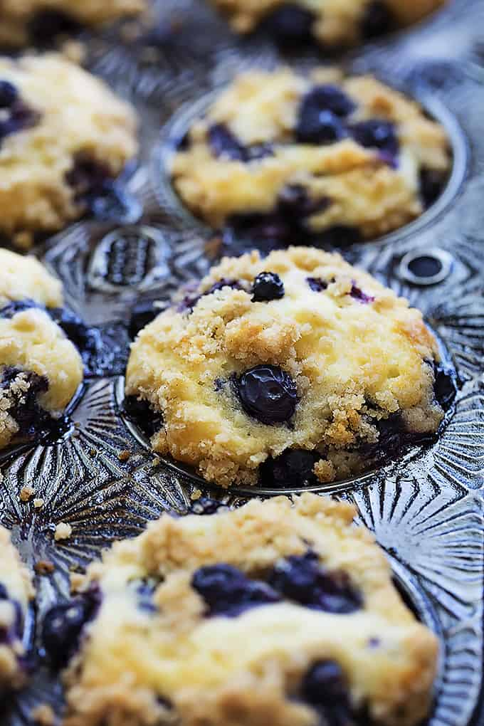 blueberry crumb muffins in a muffin tin.