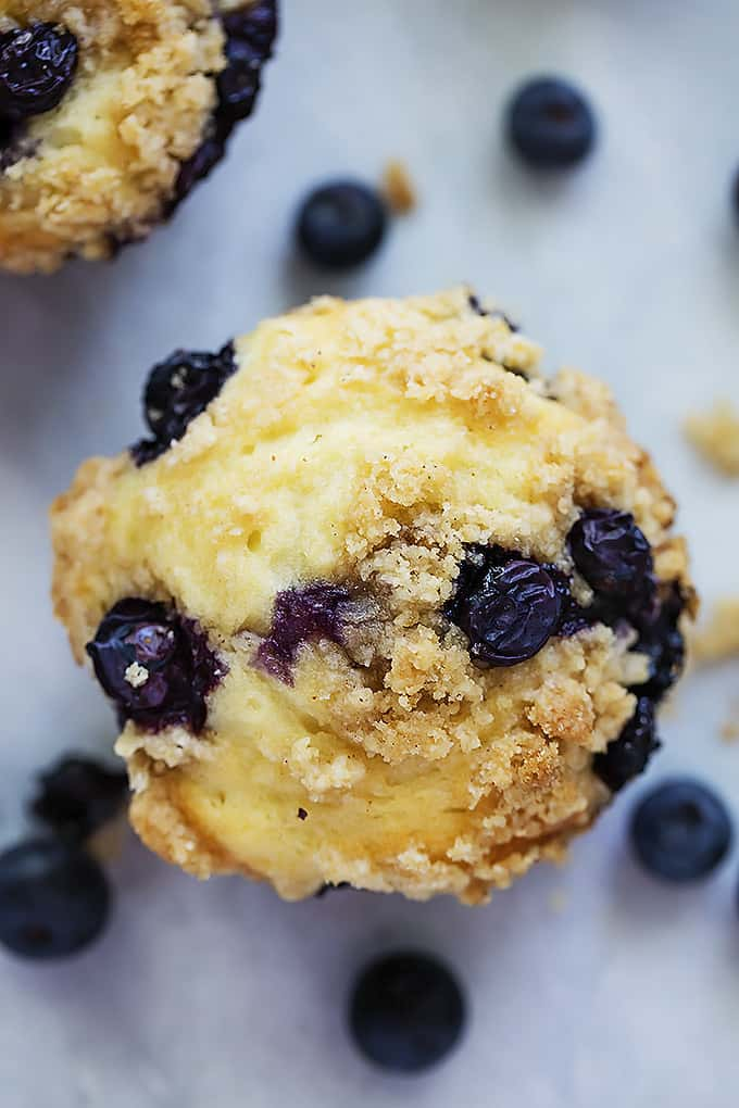 top view of a blueberry crumb muffin with blueberries around it.
