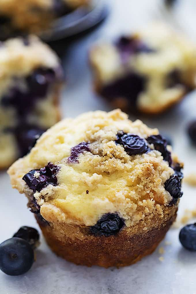 close up of a blueberry crumb muffin with more muffins in the background.