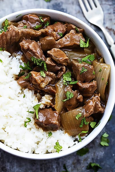 close up top view of slow cooker beef on rice in a bow with a fork on the side.