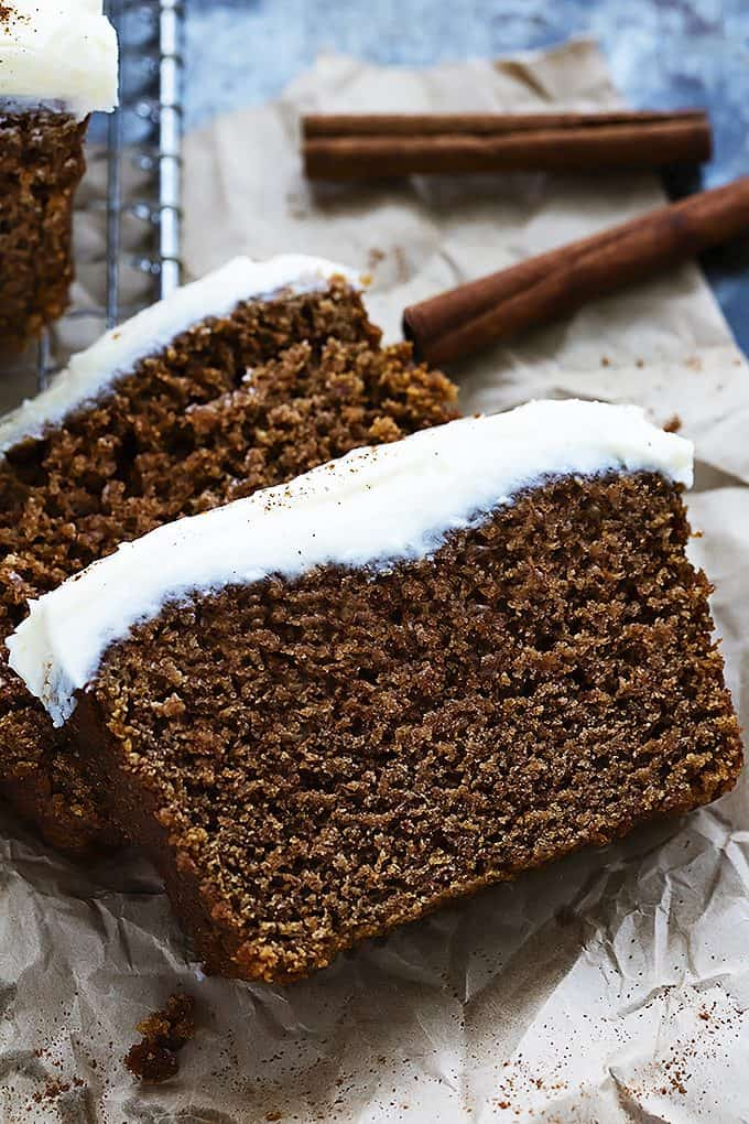 slices of gingerbread loaf with cream cheese frosting laying on top of each other with cinnamon sticks on the side.