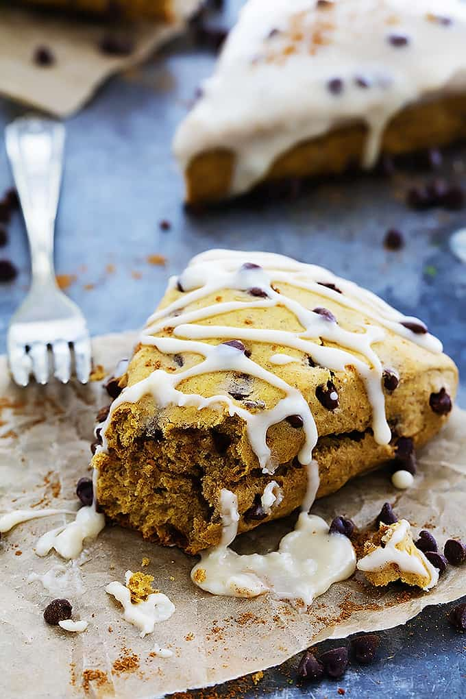 a pumpkin chocolate chip scone drizzled with cream cheese frosting with a bite missing and a fork on the side.