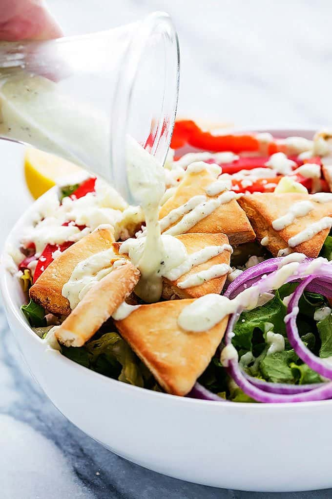 tzatziki dressing being poured on top of chicken gyro salad in a bowl.