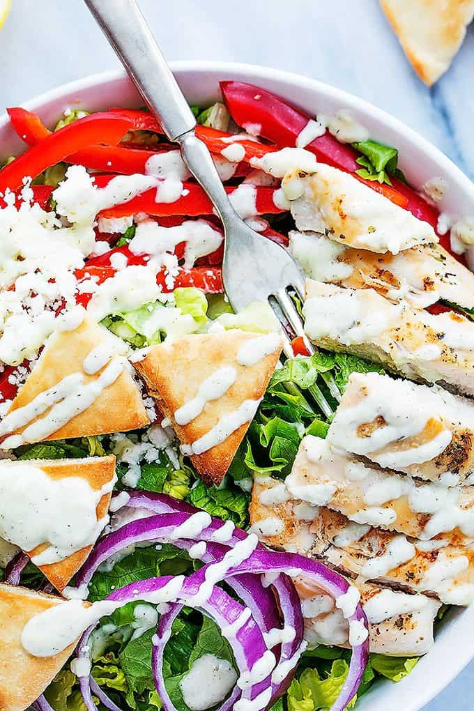 close up of chicken gyro salad with tzatziki dressing and a fork in a bowl.
