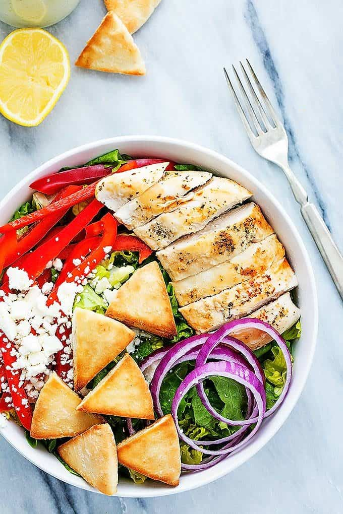 top view of chicken gyro salad with tzatziki dressing in a bowl with a half of a lemon, pita croutons and a fork on the side.