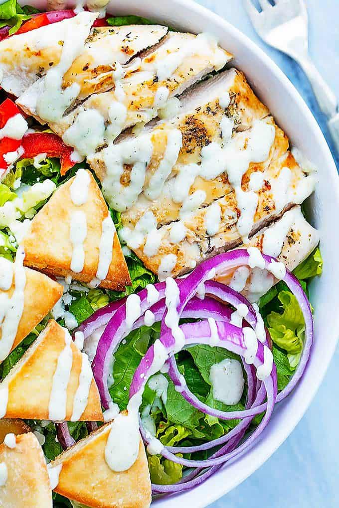 close up of chicken gyro salad with tzatziki dressing in a bowl with a fork on the side.