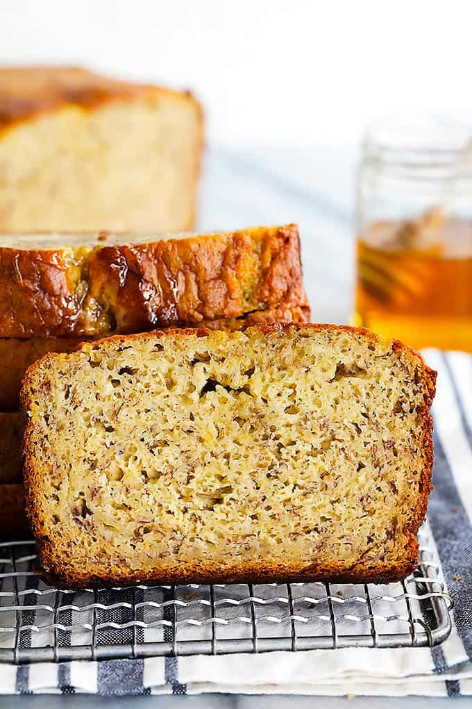 a slice of brown butter banana bread leaning on a stack of more slices of bread on a cooling rack with the rest of the loaf and a jar of honey in the background.