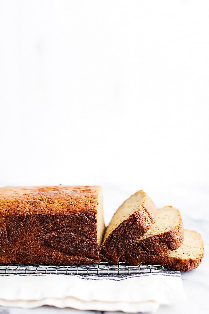 a loaf of brown butter banana bread with the front cut into slices on a cooling rack.