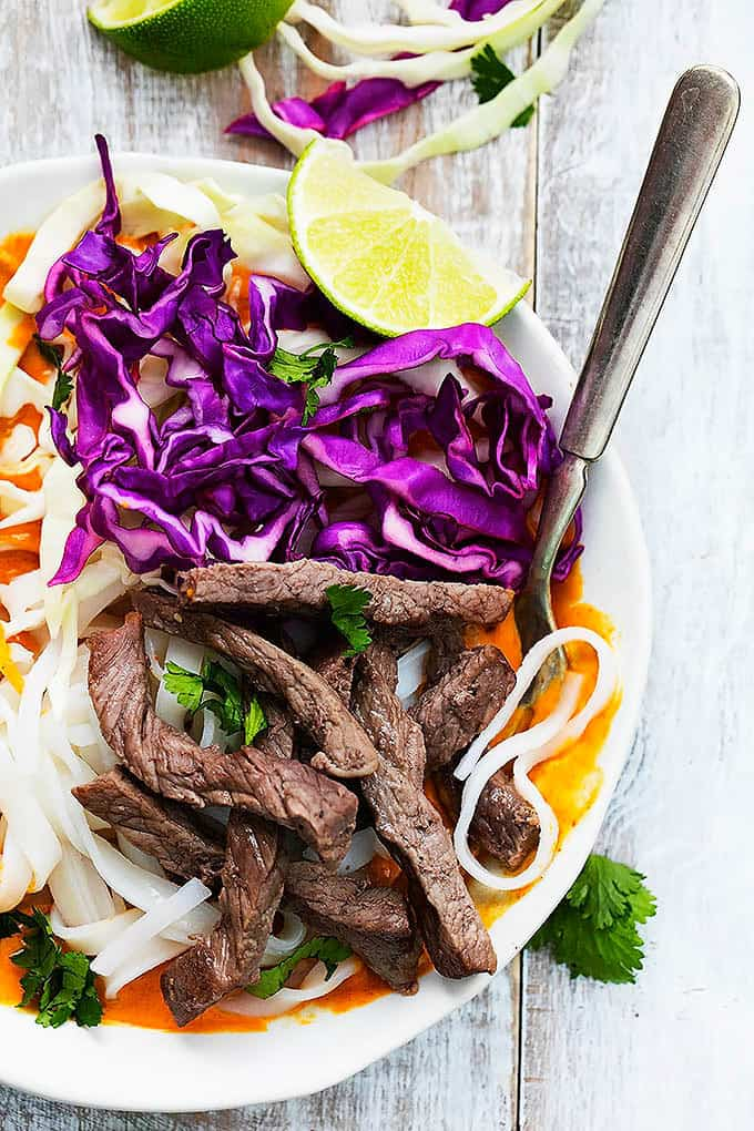 close up top view of a Thai curry steak noodle bowl with a fork inside the bowl.