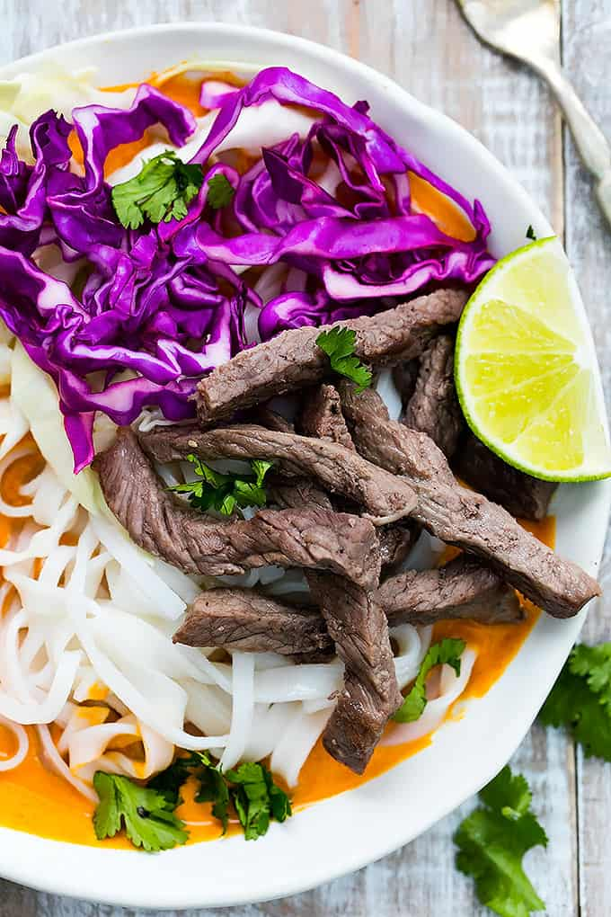 close up top view of a Thai curry steak noodle bowl with a fork on the side.