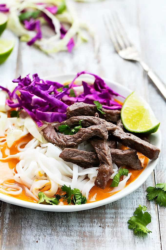 a Thai curry steak noodle bowl with a fork on the side.