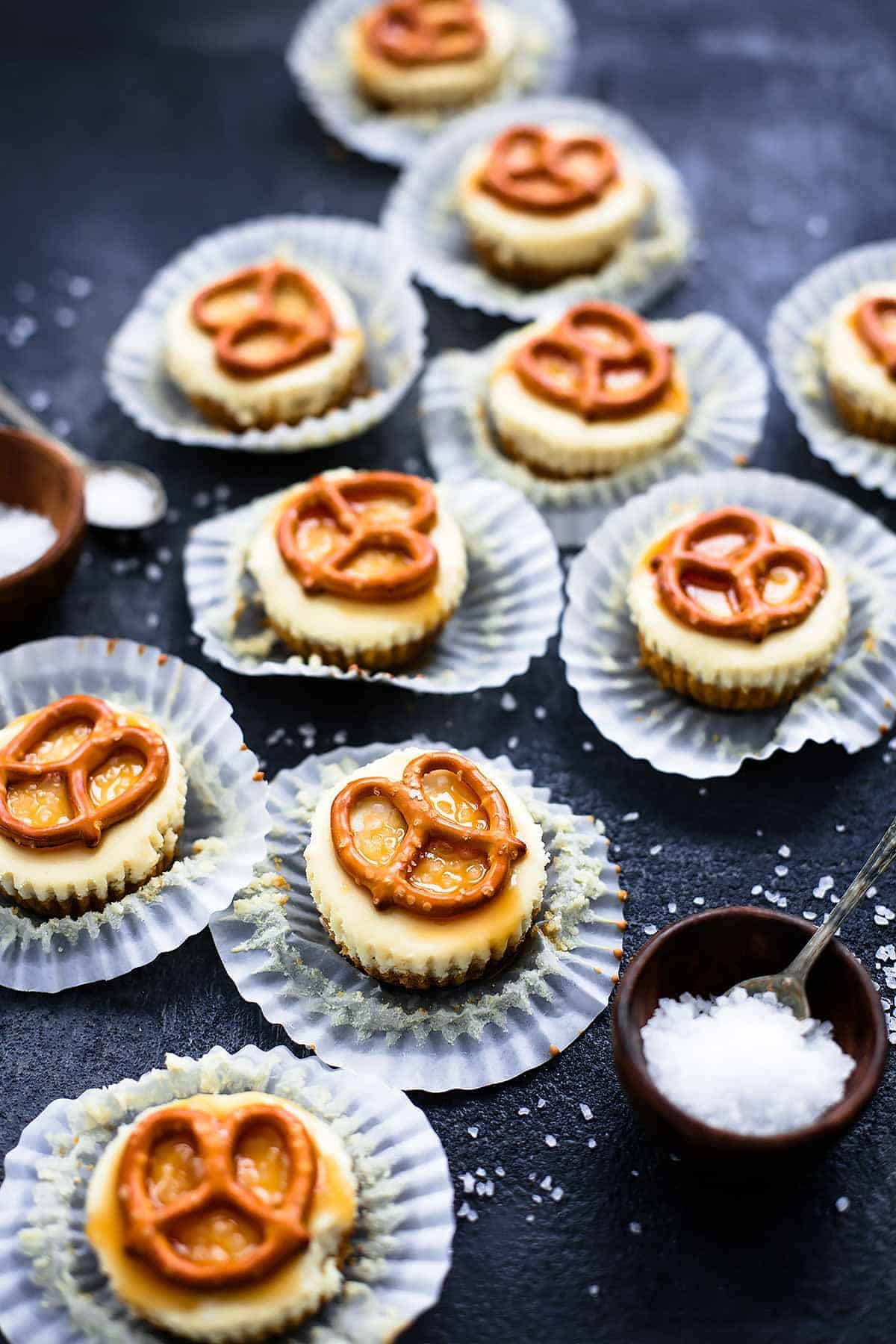 salted caramel pretzel mini cheesecakes with their liners open with small bowls and spoons with salt on top on the side.