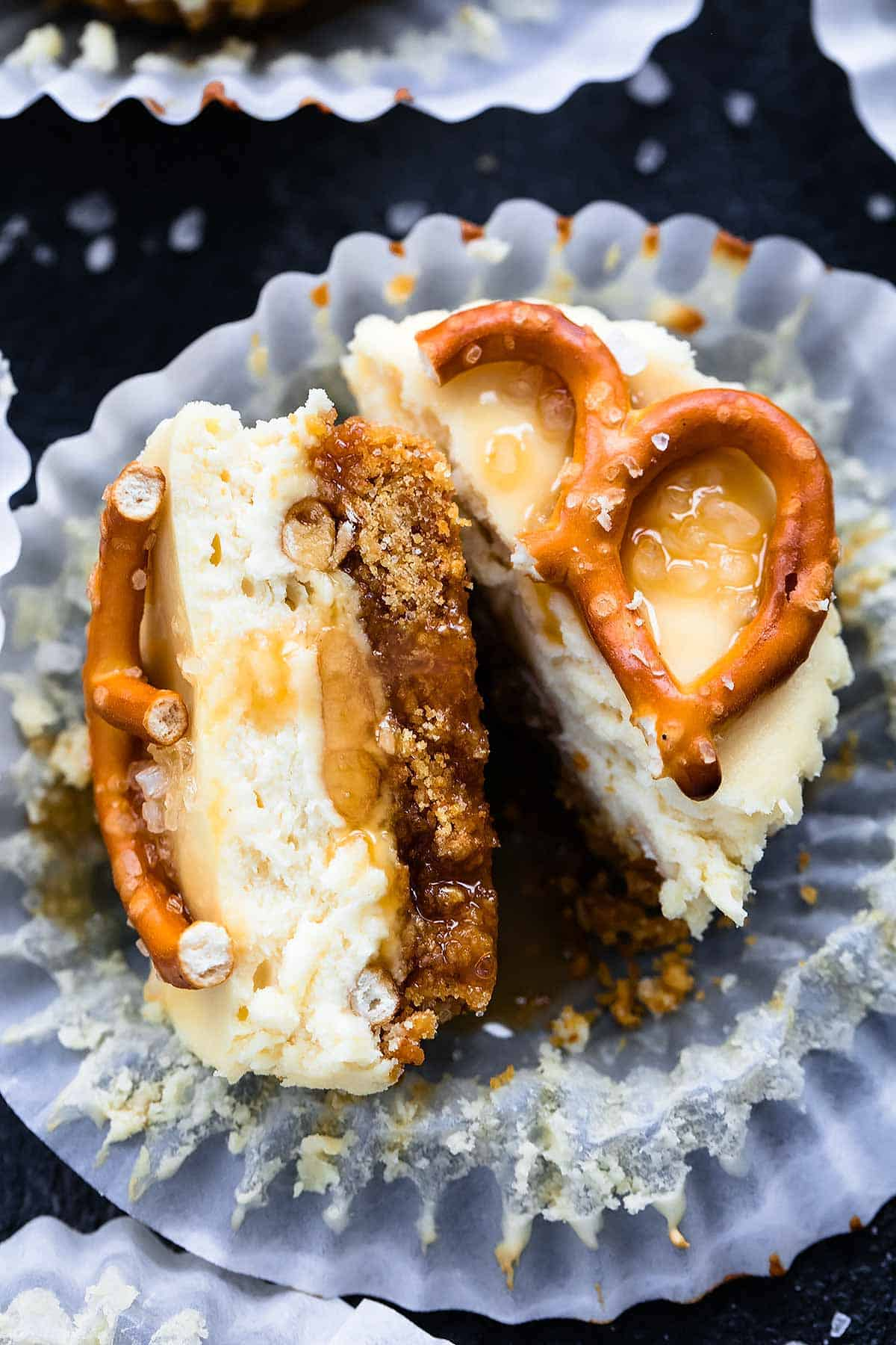 close up of a salted caramel pretzel mini cheesecake cut in half with the liner opened.