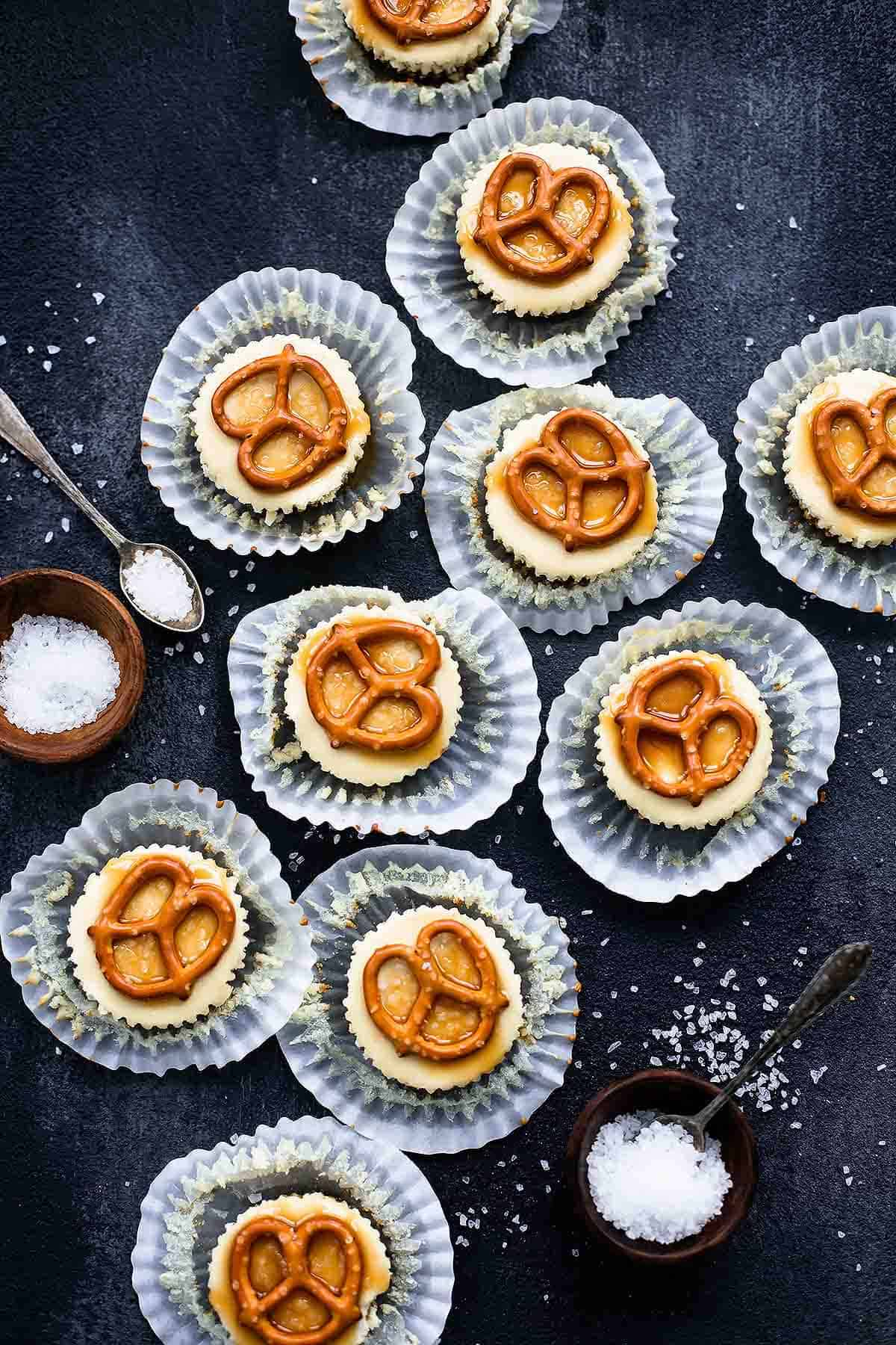 top view of salted caramel pretzel mini cheesecakes with their liners open with salt in small bowls and on spoons on the side.