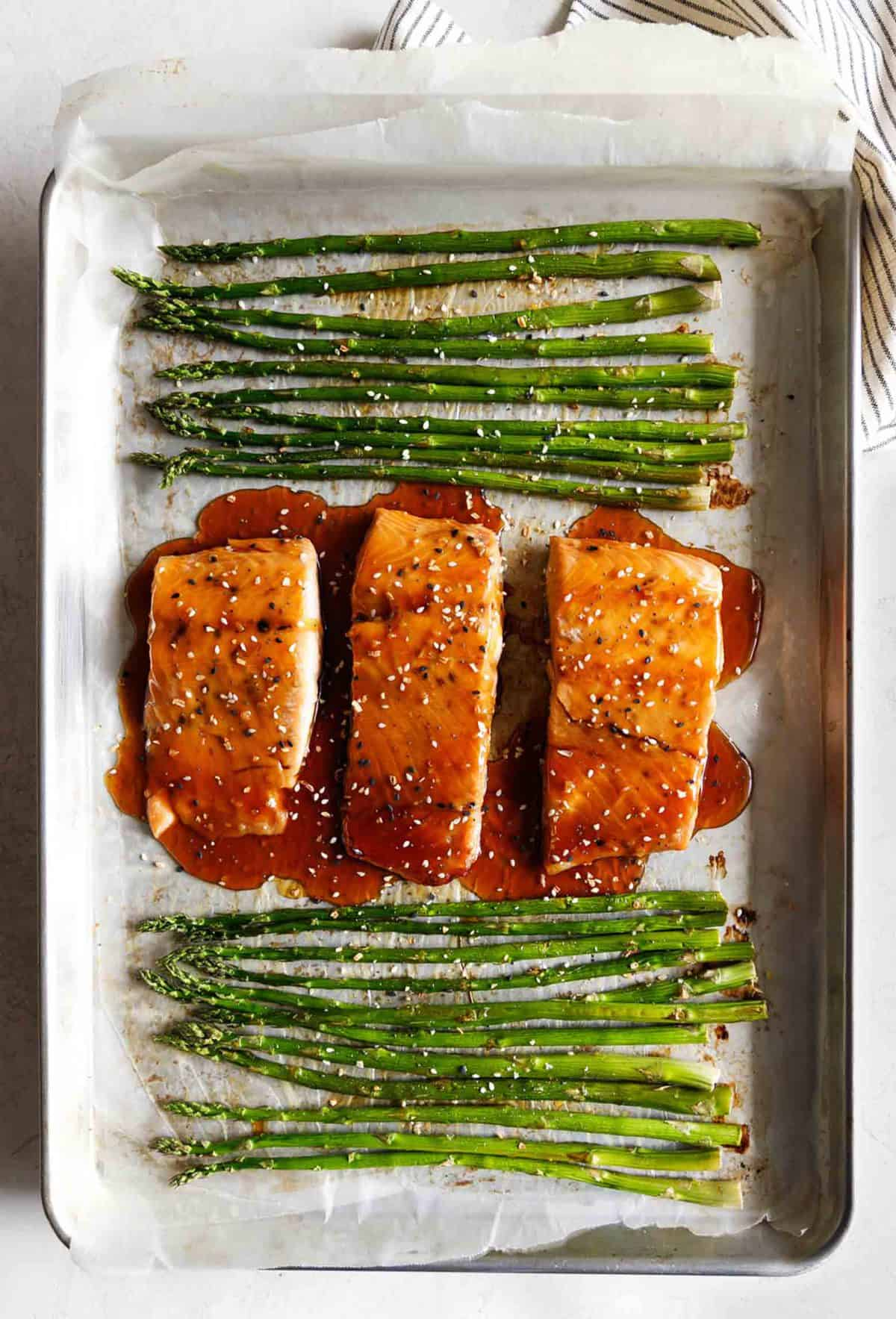 top view of baked sesame glazed salmon and asparagus on a baking sheet.