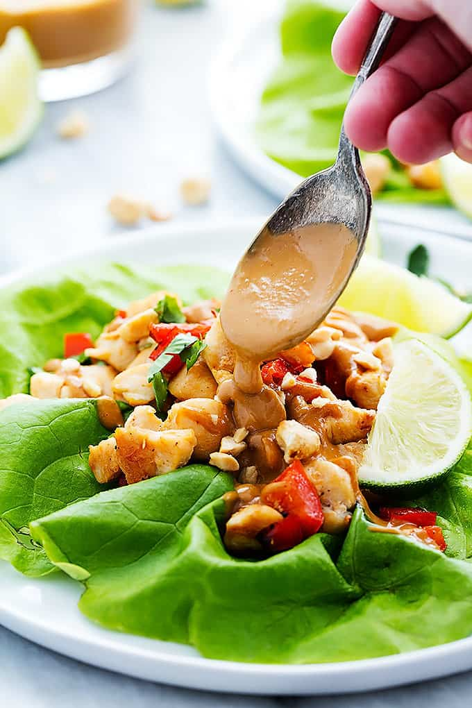 a hand putting peanut sauce on a Thai peanut chicken lettuce wrap with a spoon.