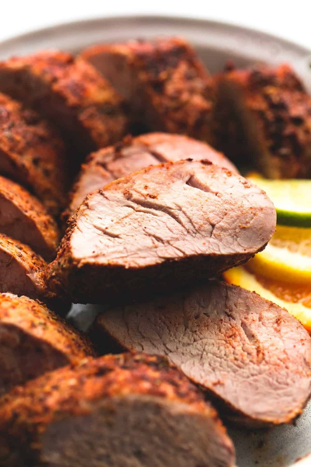 Up close sliced pork tenderloin on a plate with lemon, lime, and orange slices