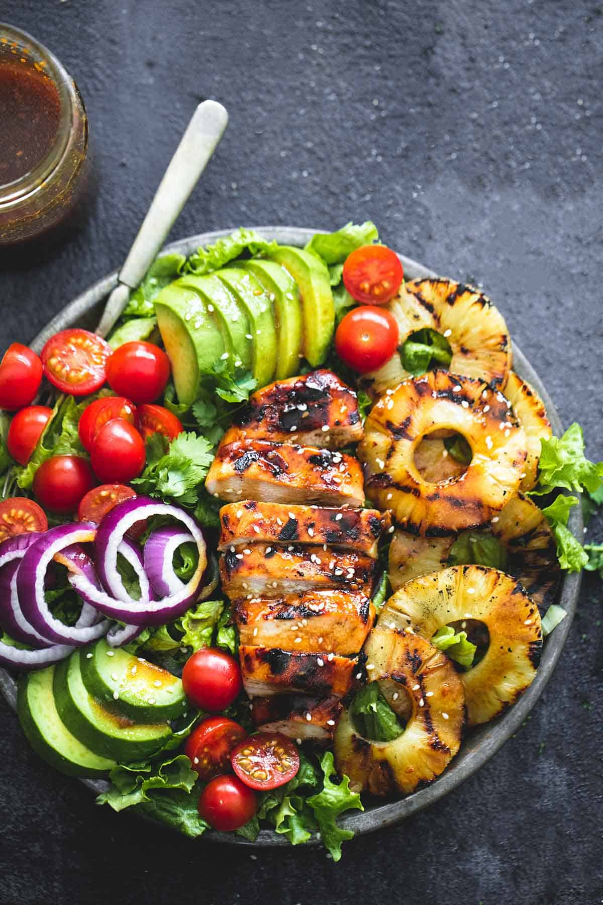 top view of grilled teriyaki chicken salad with a fork on a plate with a jar of teriyaki vinaigrette on the side.