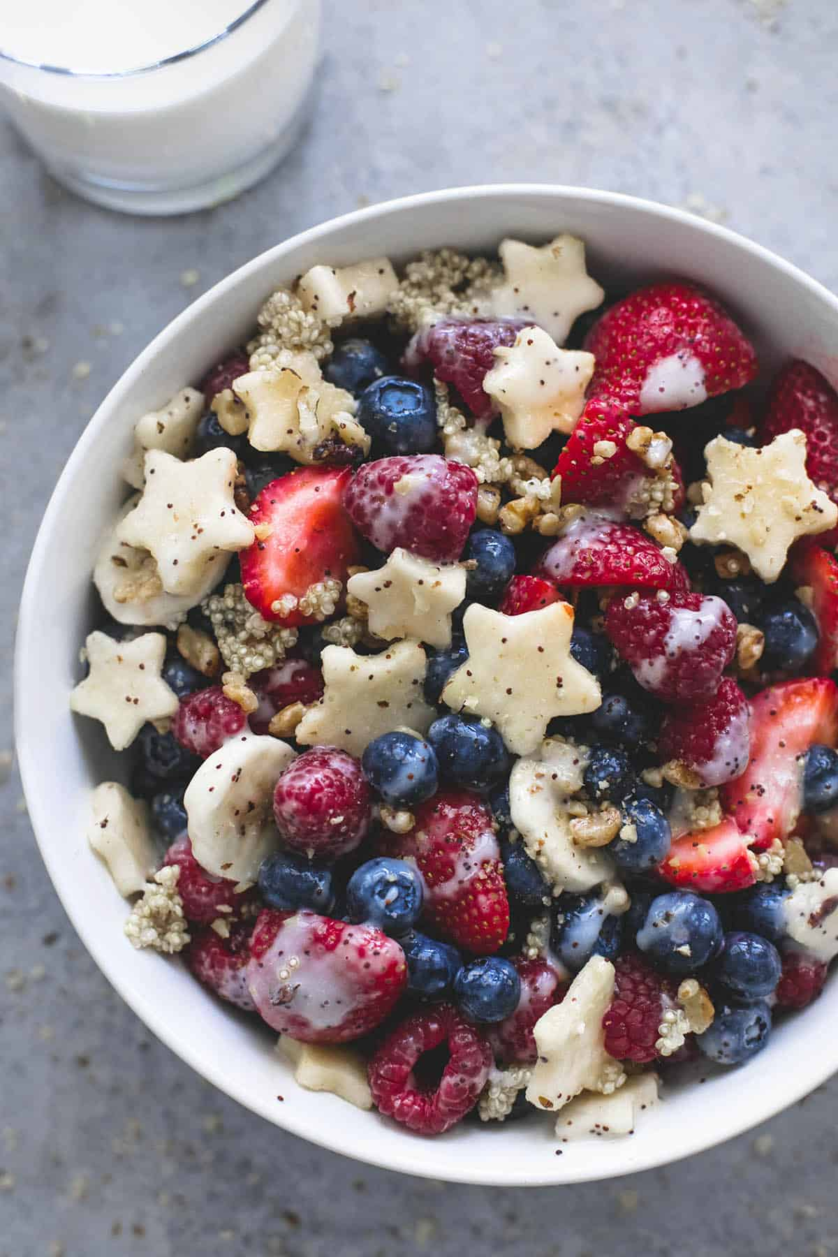 top view of Patriotic fruit salad with honey lime dressing in a bowl with a glass of honey lime poppyseed dressing.
