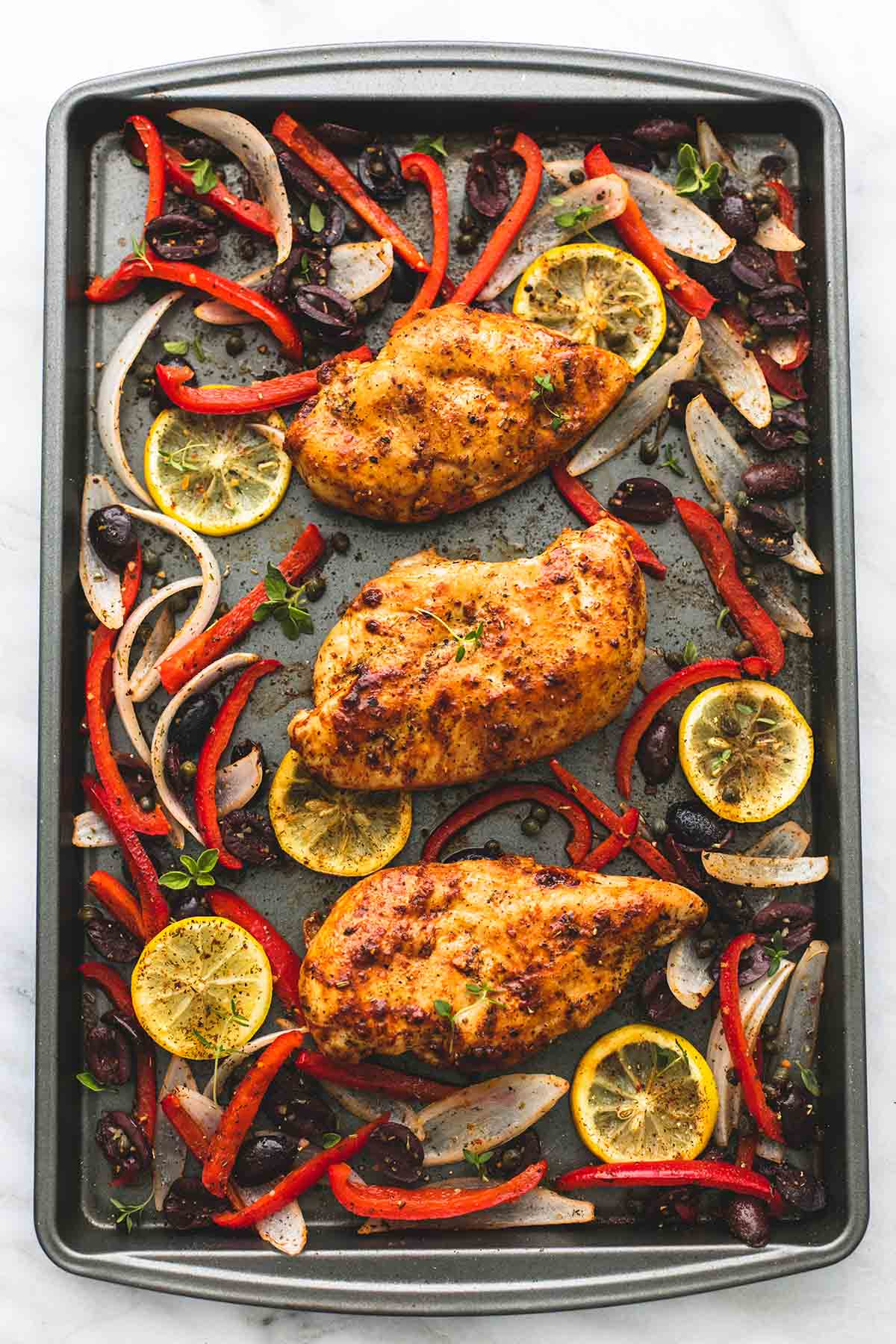 top view of baked Greek chicken sheet pan dinner on a baking sheet.