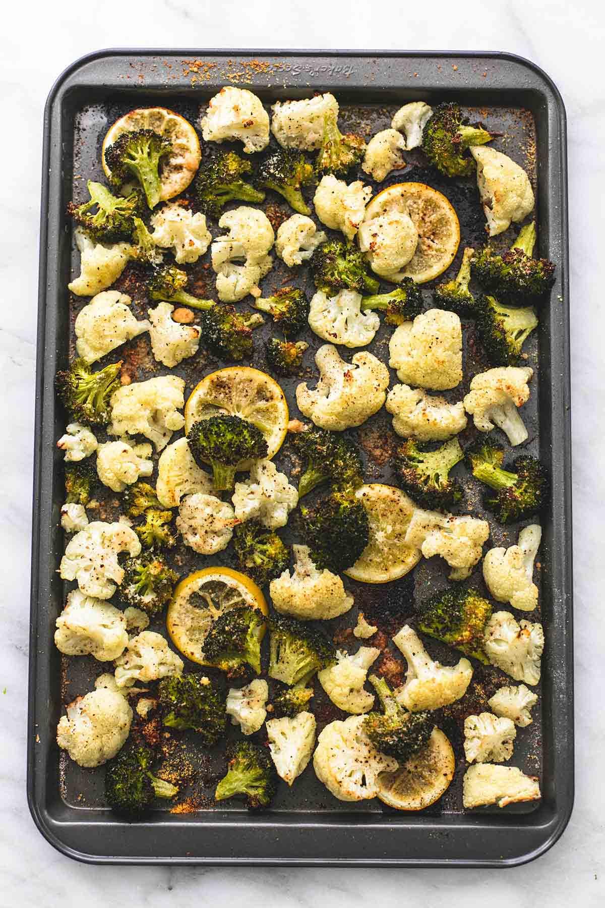 top view of roasted lemon garlic broccoli & cauliflower on a baking sheet.