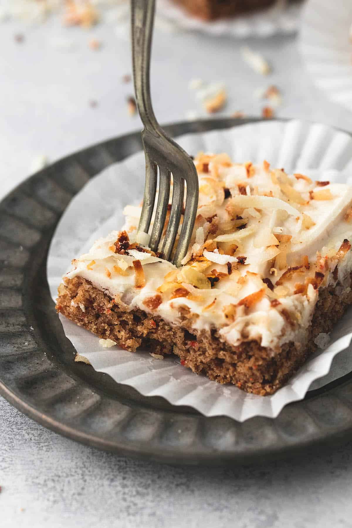 a carrot cake bars with coconut cream cheese frosting on a liner and on a plate with a fork in it.