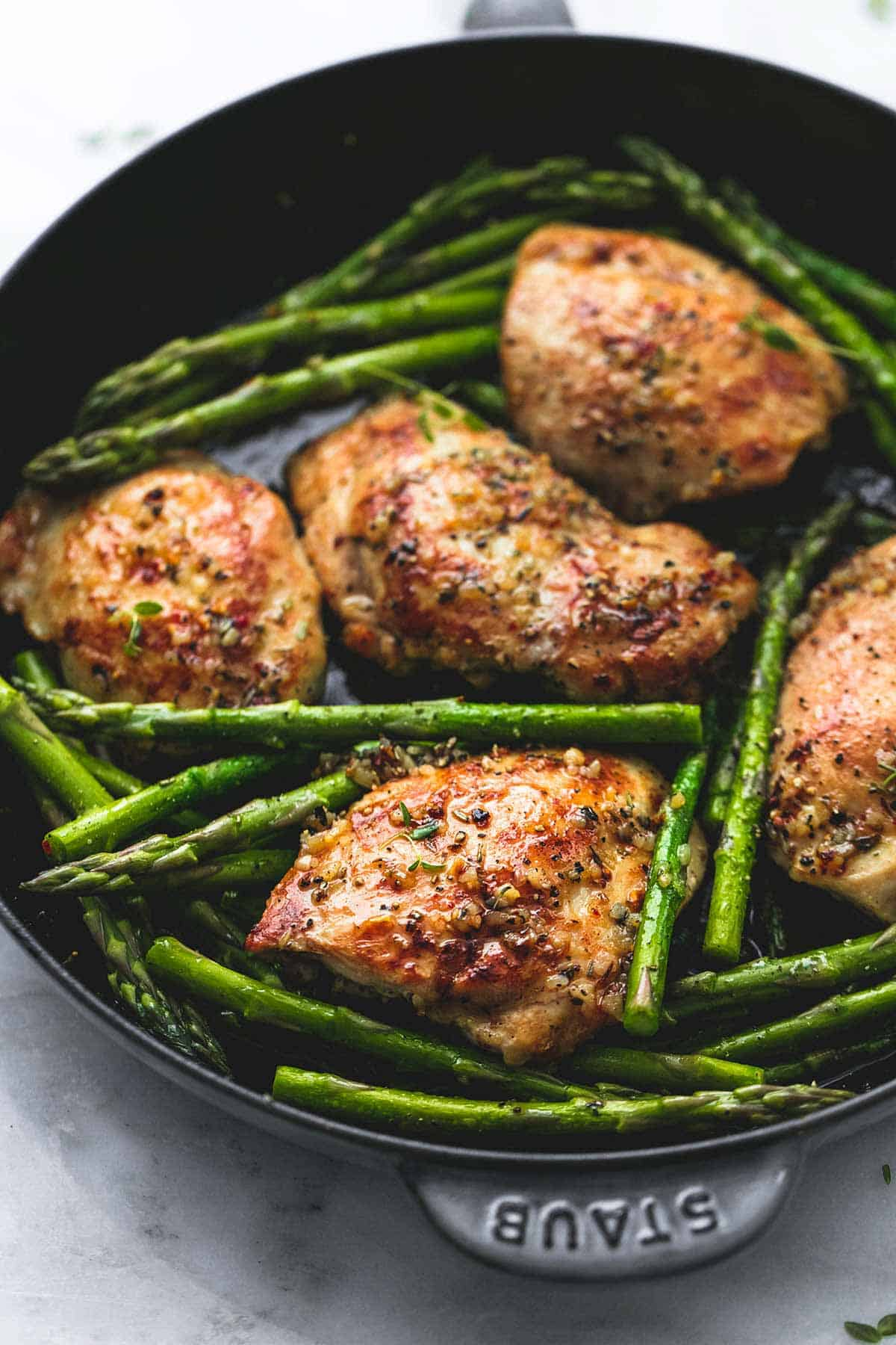 garlic herb chicken and asparagus in a pan.