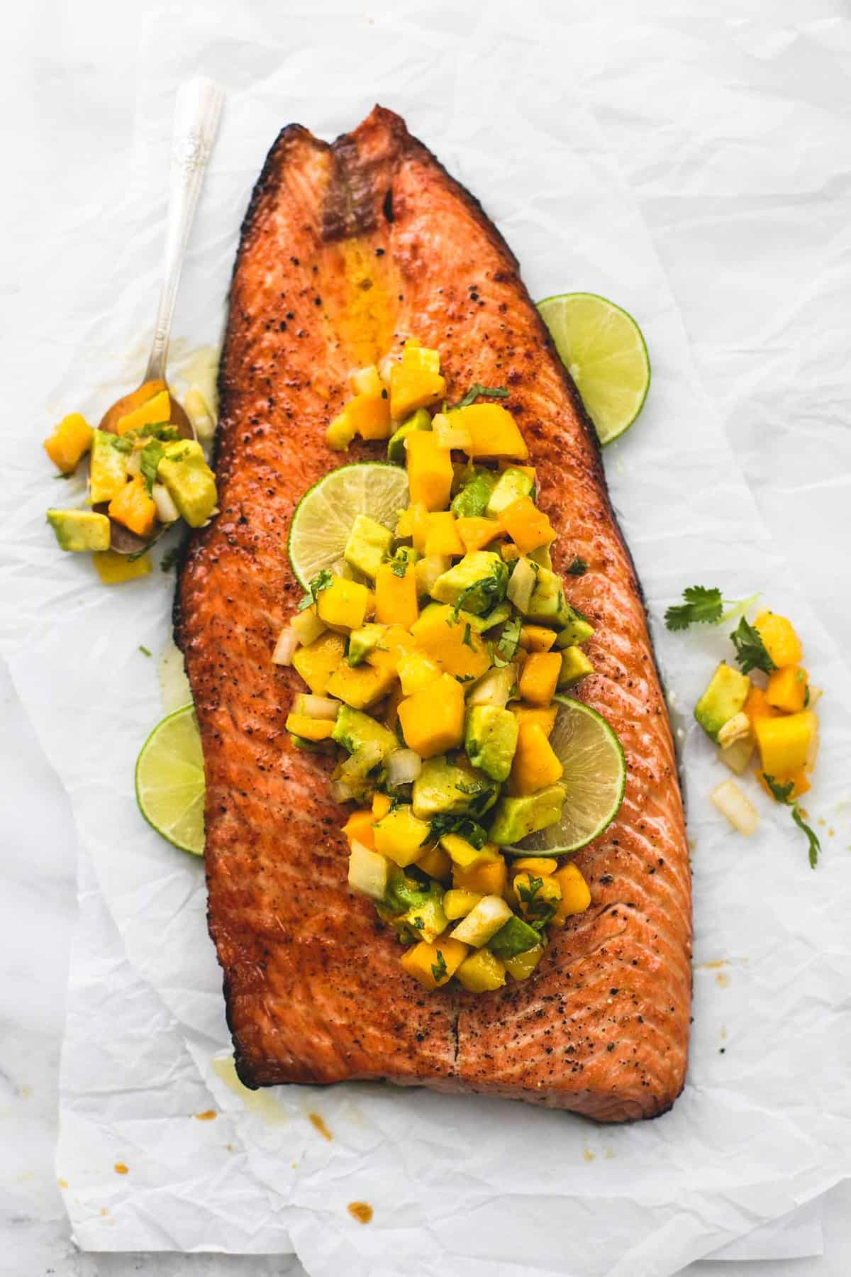 top view of grilled honey lime salmon with mango avocado salsa and lime slices.