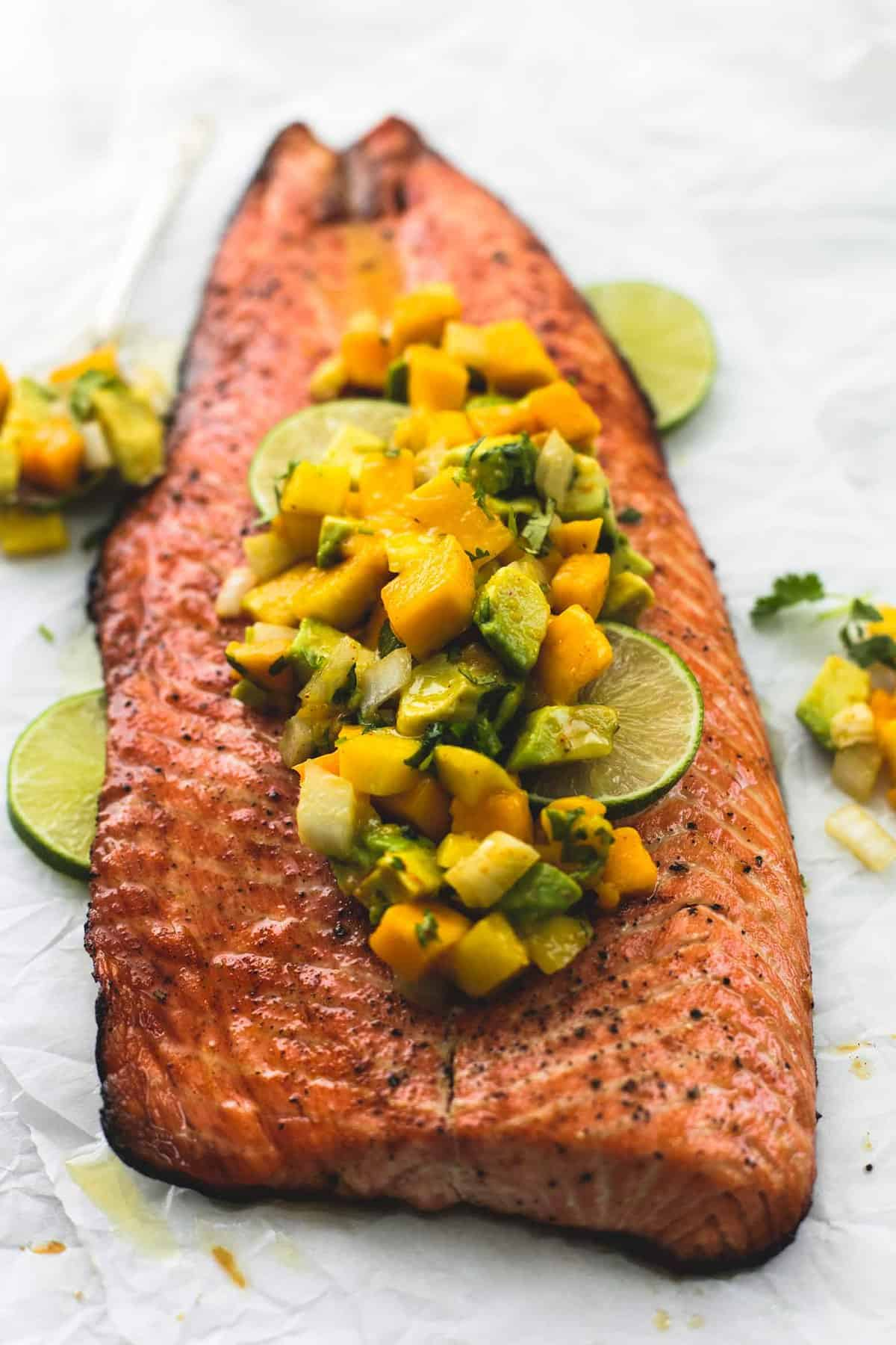 grilled honey lime salmon with mango avocado salsa and lime slices.