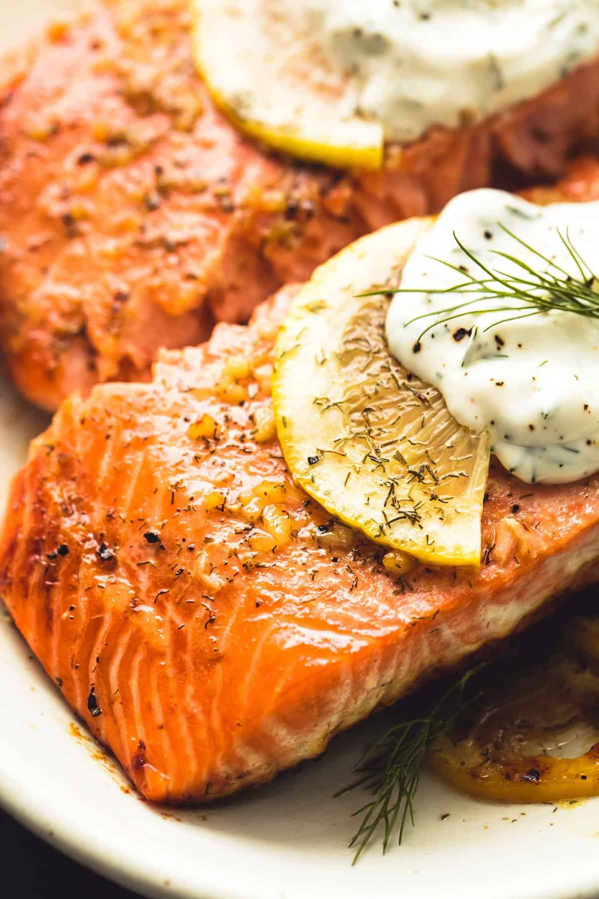 close up of baked salmon with creamy lemon dill sauce on a plate.