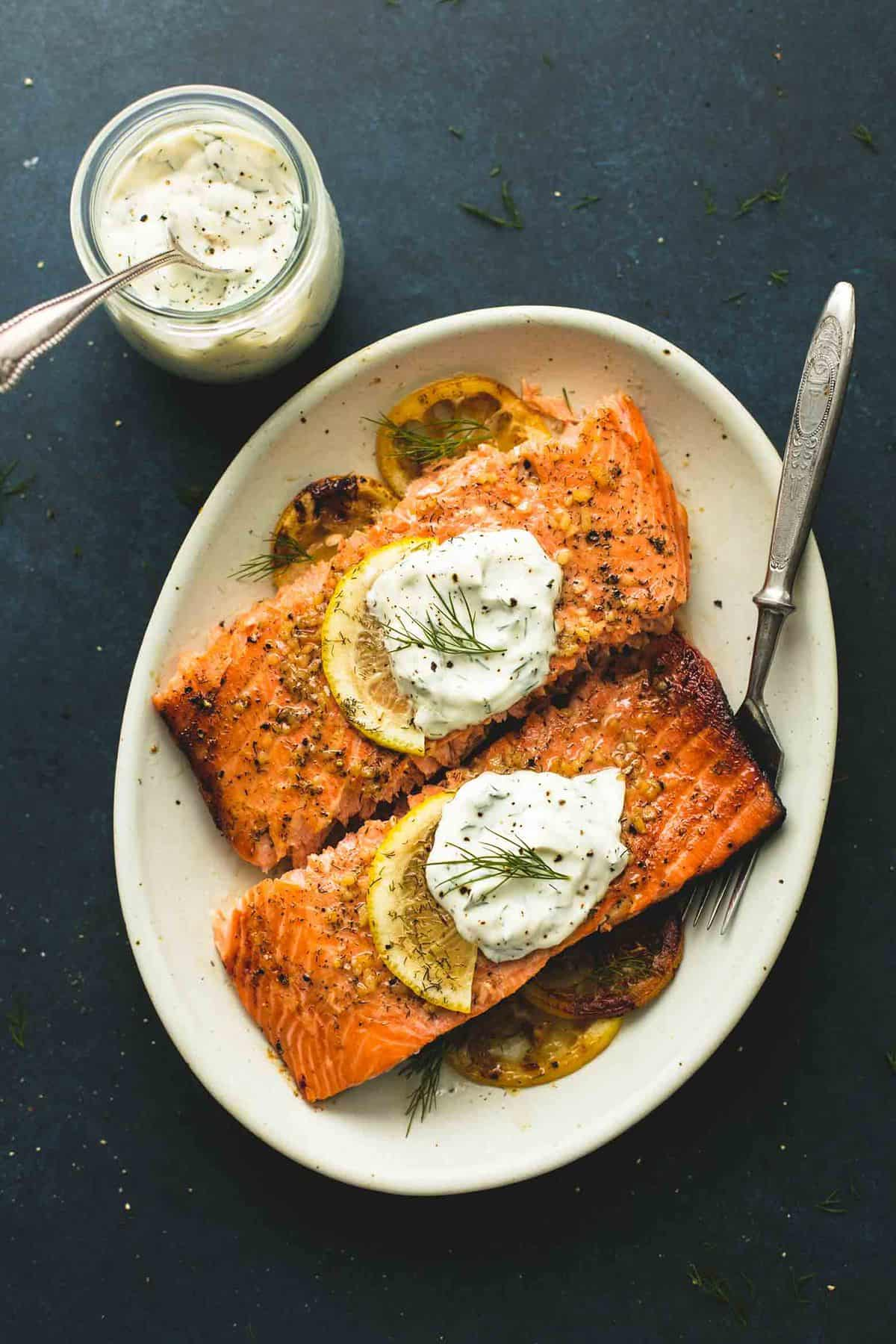 top view of baked salmon with creamy lemon dill sauce with a fork on a plate with a jar of more sauce with a spoon on the side.