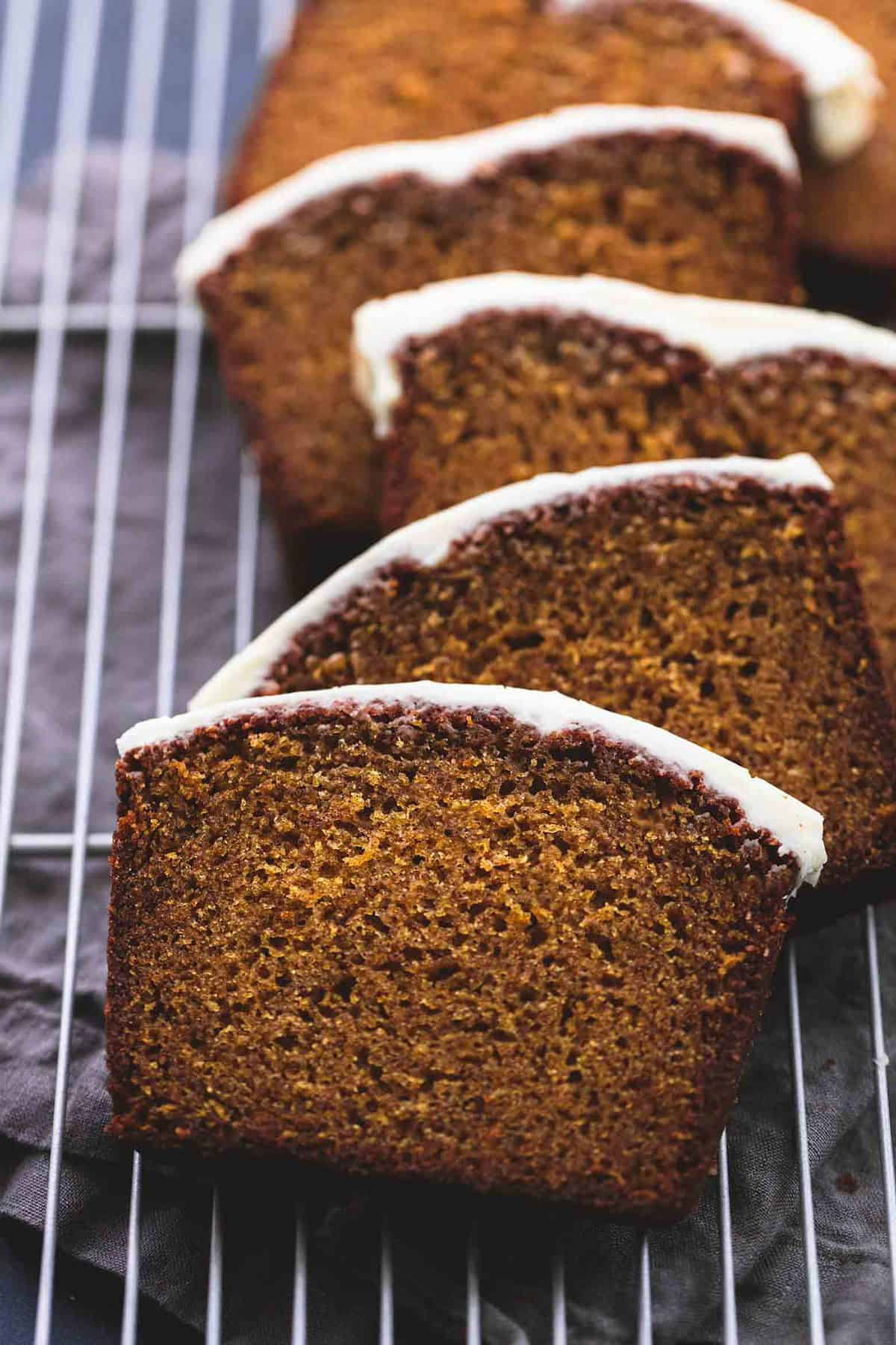 cream cheese frosted pumpkin bread slices on a cooling rack.