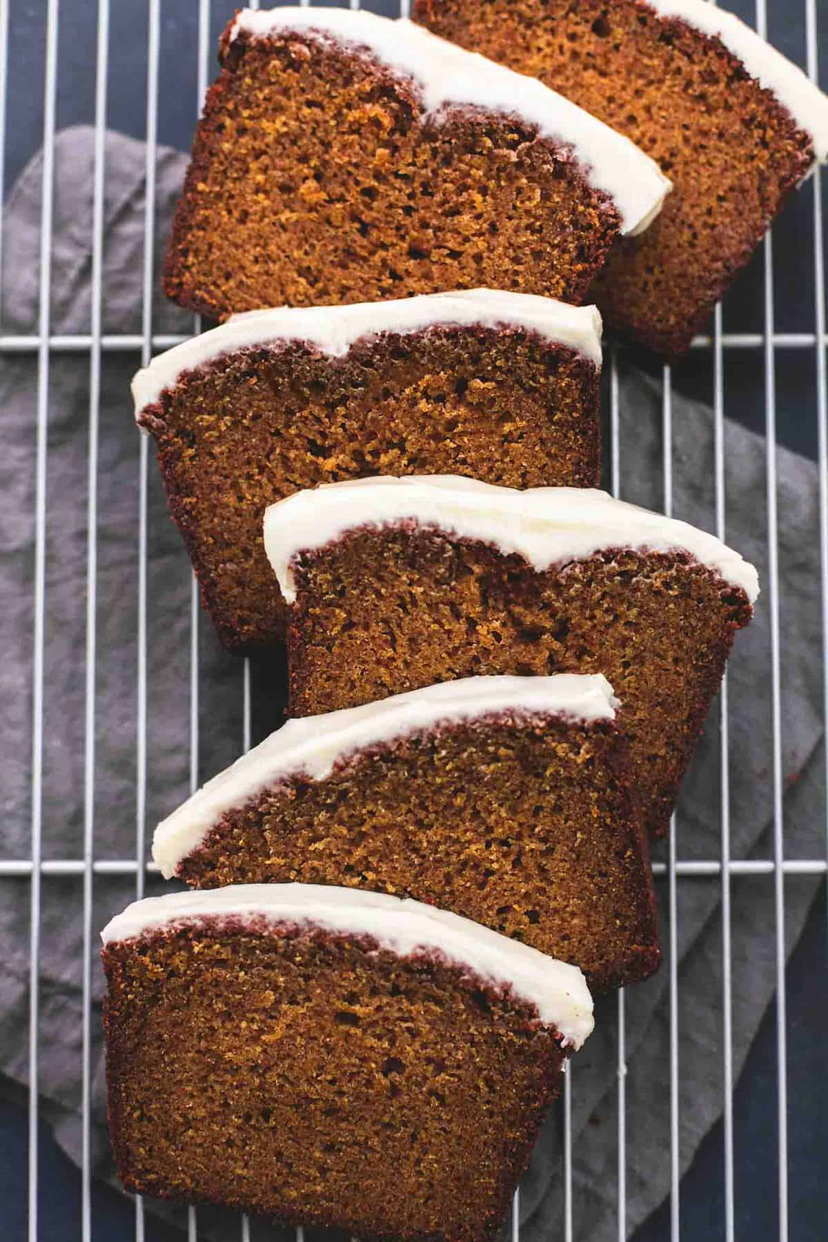 top view of slices of cream cheese frosted pumpkin bread on a cooling rack.