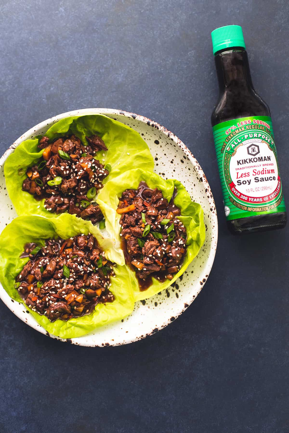 top view of honey beef lettuce wraps on a plate with a bottle of Kikkoman soy sauce on the side.