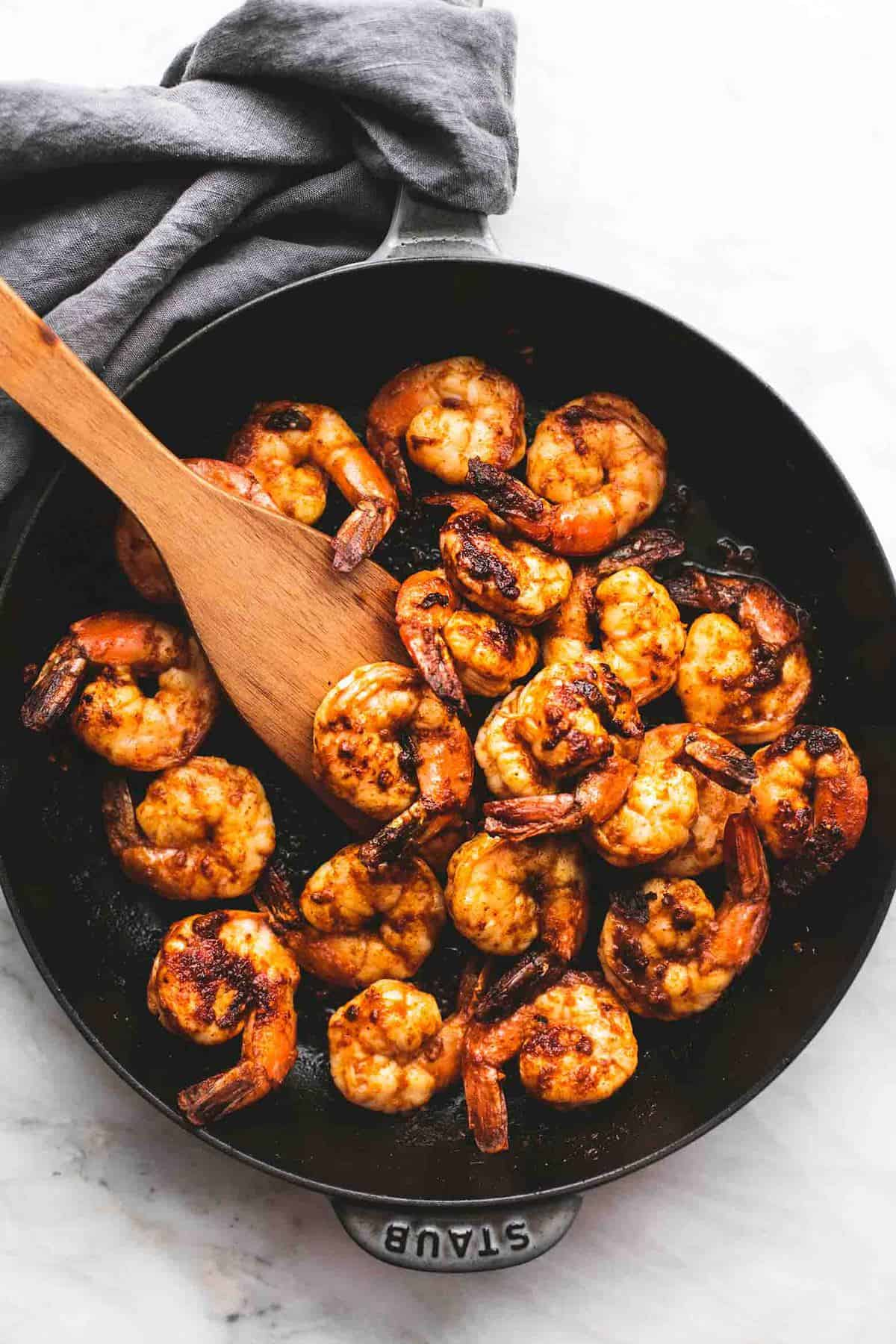 top view of fiesta lime shrimp in a wooden serving spoon in a pan.