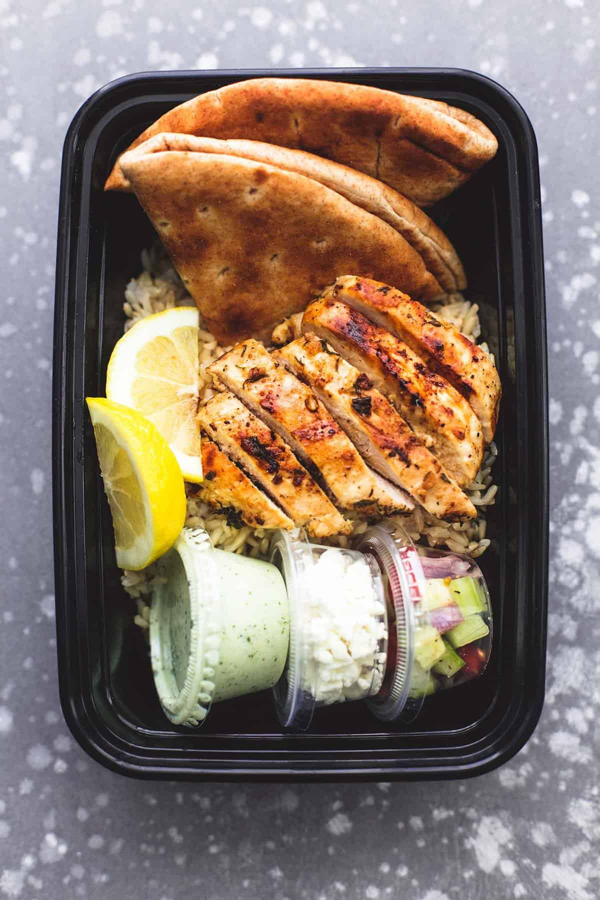 top view of meal prep Greek chicken gyro bowl in a tupperware container.