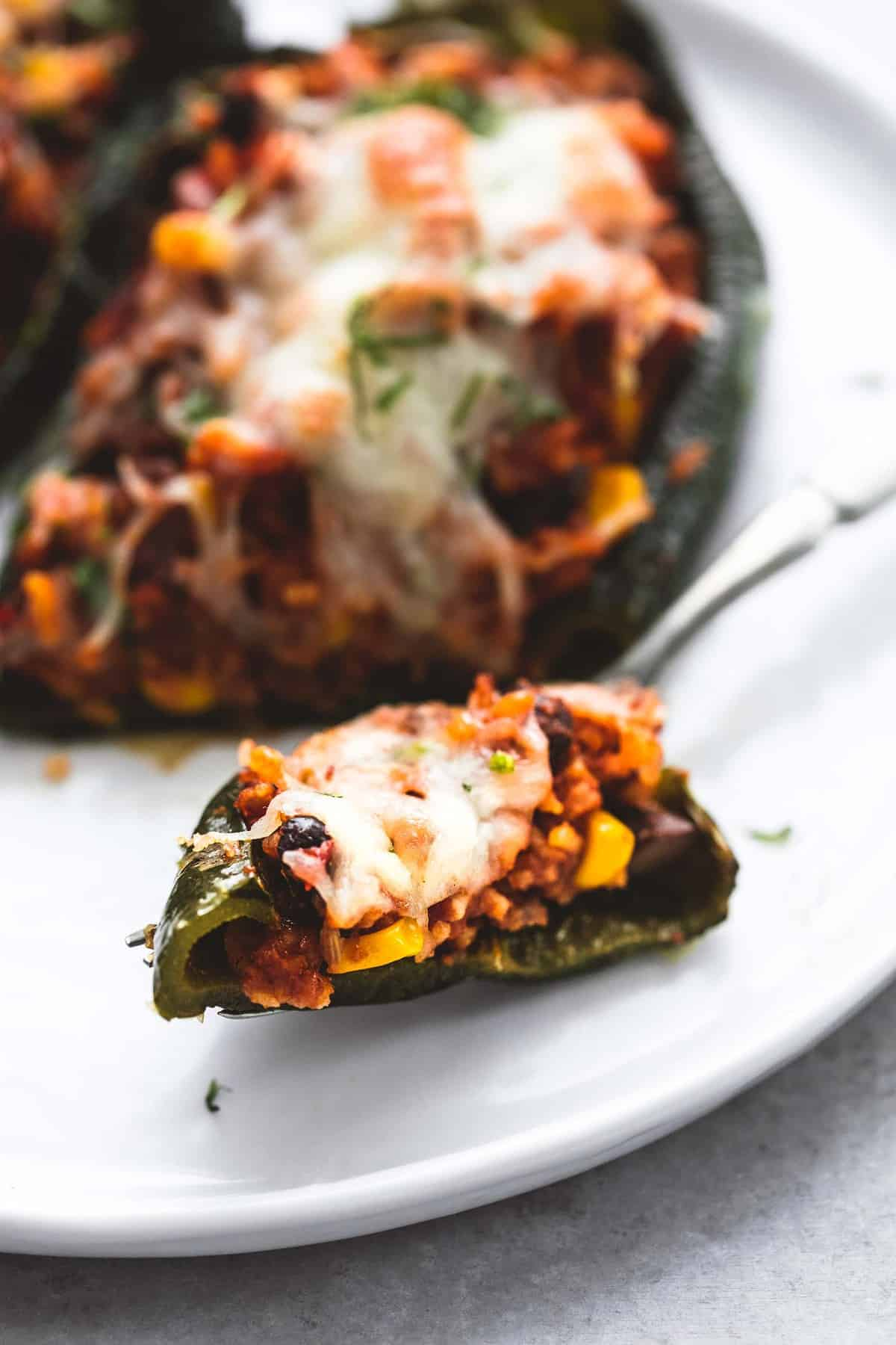 close up of a bite of Southwest stuffed poblano peppers on a fork with stuffed peppers in the background all on a plate.