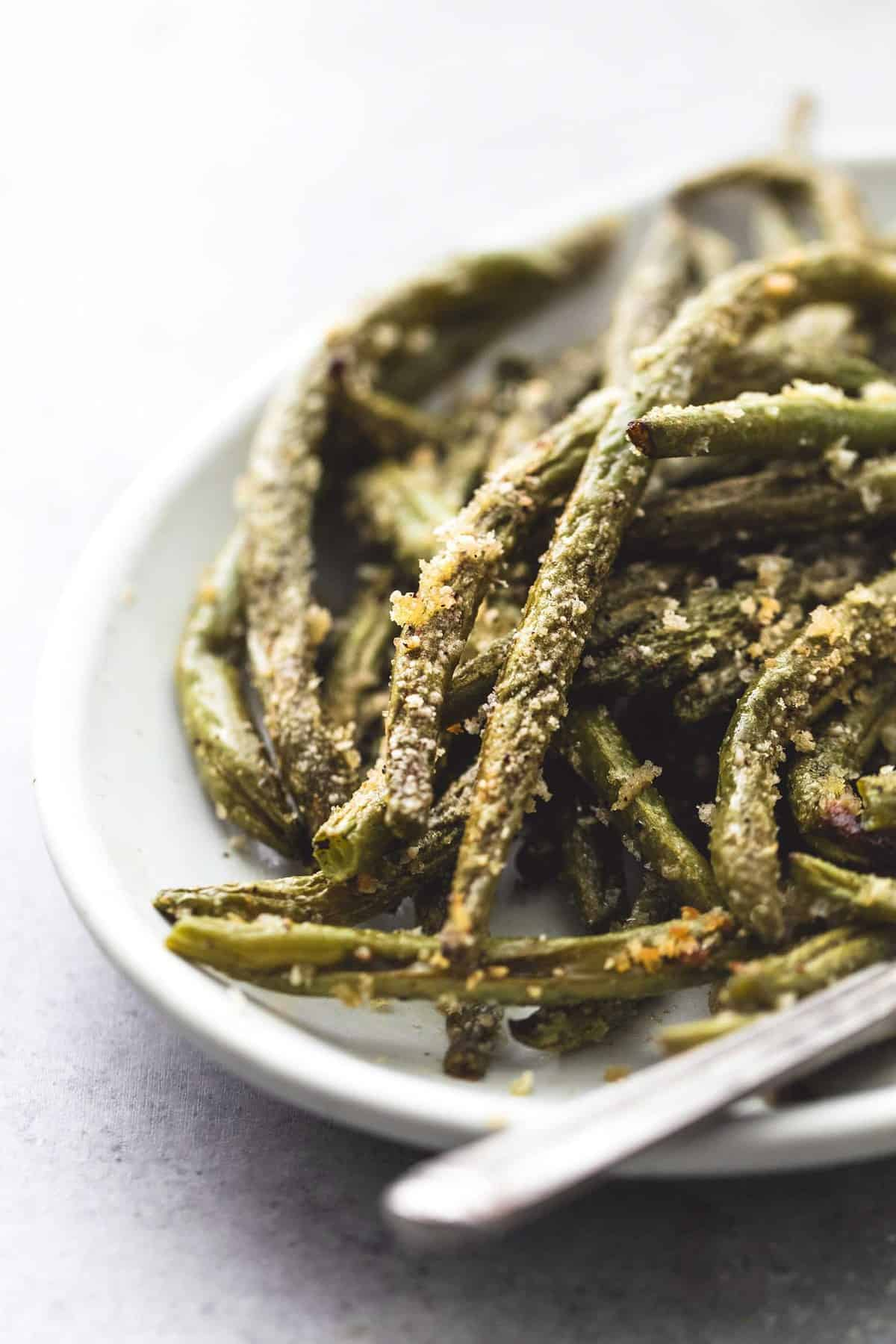 Easy, oven roasted Crispy Parmesan Green beans with savory garlic and herb seasonings and a crispy parmesan coating that is irresistible. | lecremedelacrumb.com