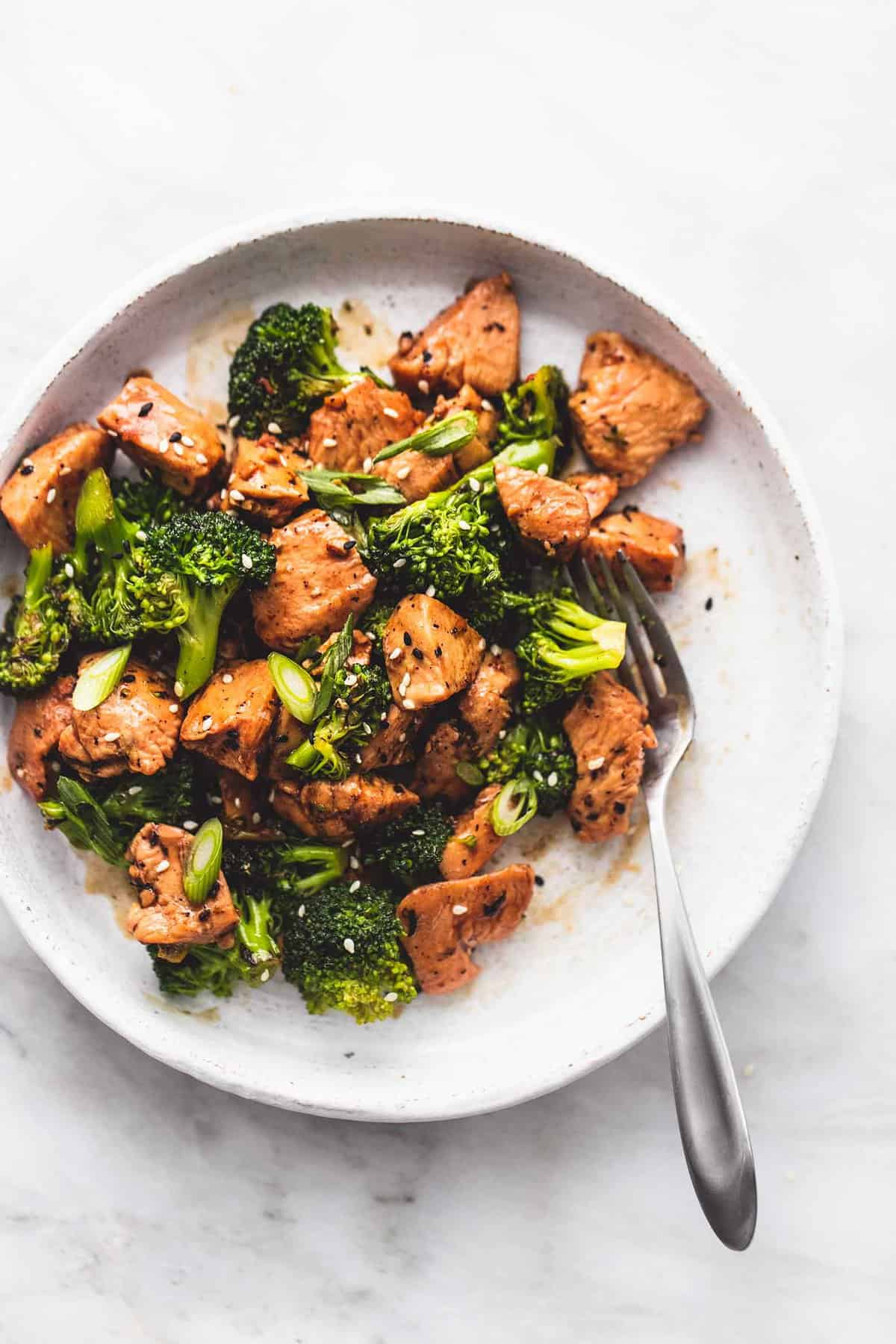 top view of chicken and broccoli stir fry with a fork on a plate.