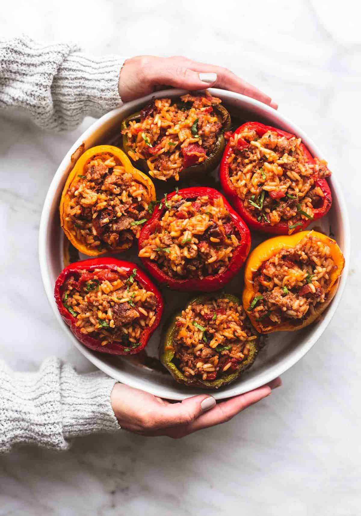 top view of hands holding a round dish of stuffed peppers.