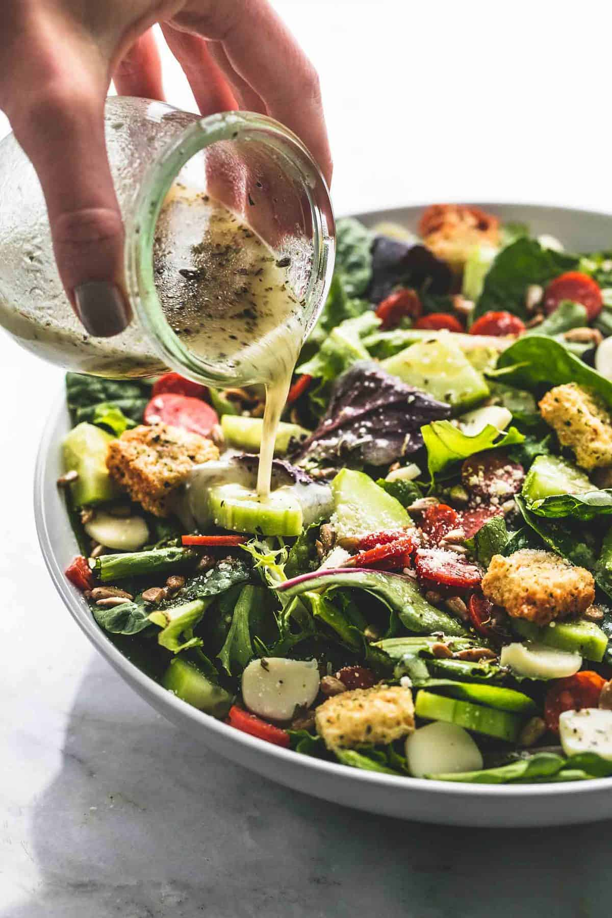 a hand pouring a jar of dressing on top of Italian green salad in a bowl.