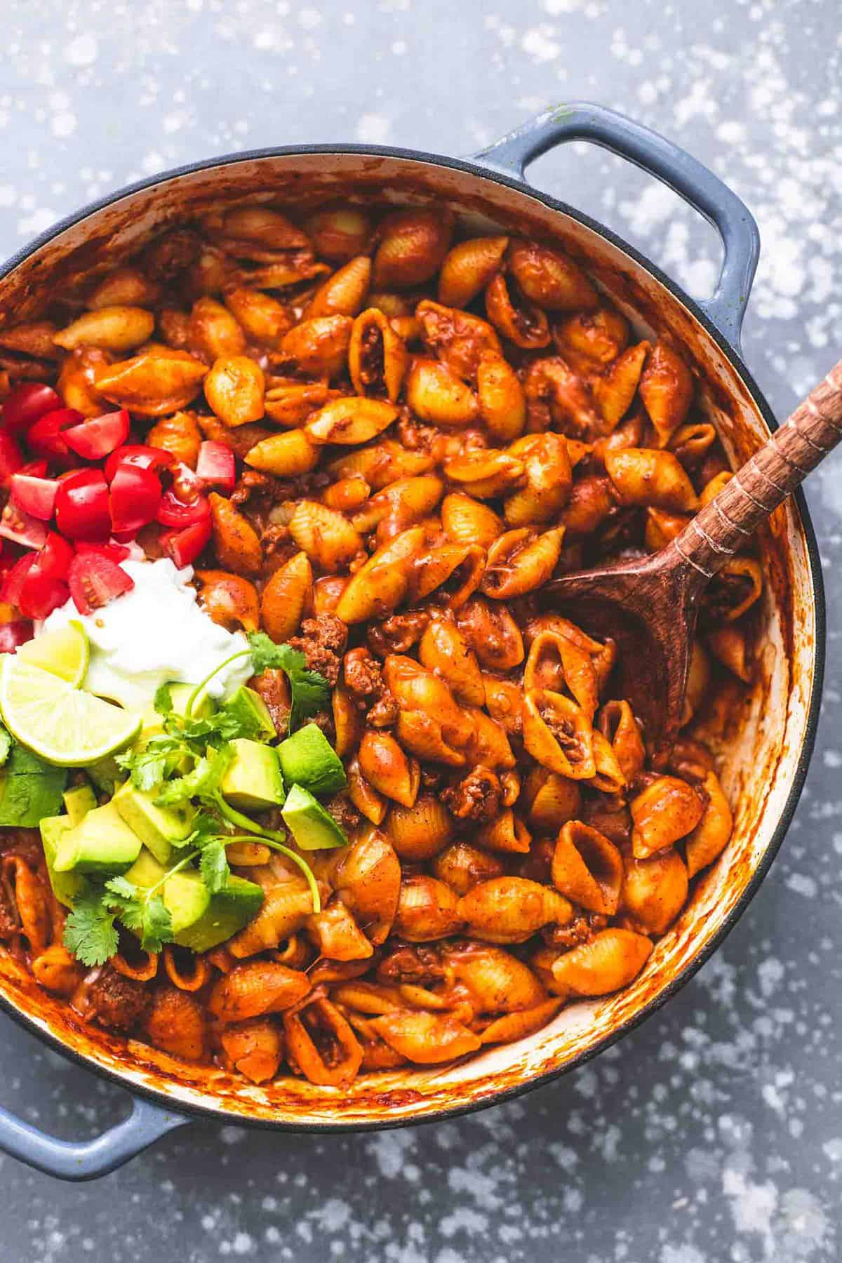 top view of beefy enchilada shells with taco toppings and a wooden serving spoon on the sides all in a pan.